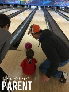 Daddy teaching them how to bowl.